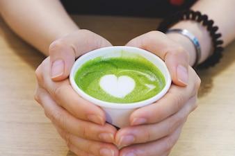 Closeup hot greentea with heart shape in woman hand