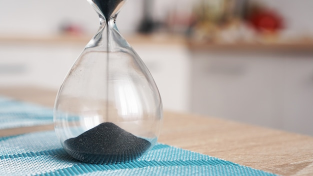 Closeup of hourglass on a white wooden table with defocus kitchen. concept of time to cook.
