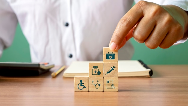 Closeup of human hand stacking wooden blocks overlapping health care icons and medical icons