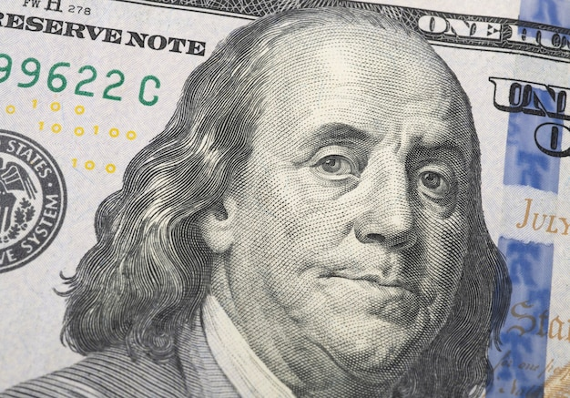 Closeup of a hundred dollars bill showing benjamin franklin.