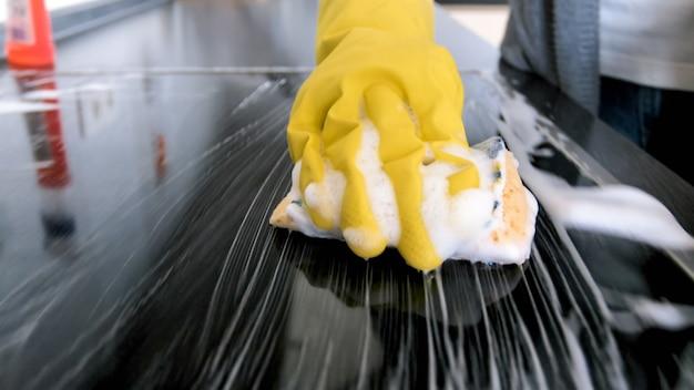 スポンジと洗剤で電気ストーブを洗うゴム手袋のyougnwoamnのクローズアップ画像。 Premium写真