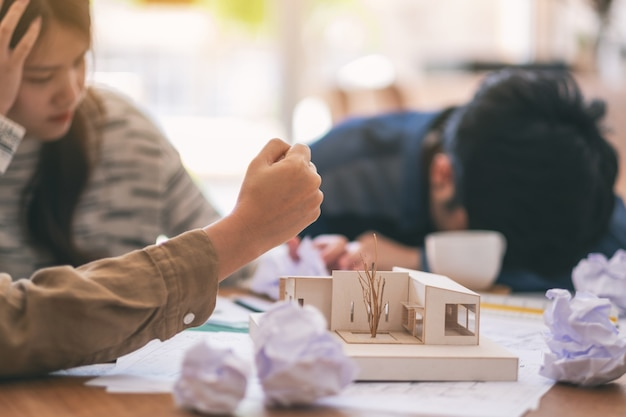 Closeup image of an angry and stressed architects try to destroy an architecture model on the table by hand when fail at work