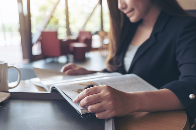 Closeup image of an asian businesswoman reading a book with coffee cup on table in cafe