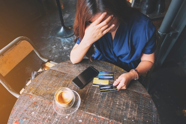 Closeup image of an asian woman get stressed and broke while holding credit card with mobile phone on the table