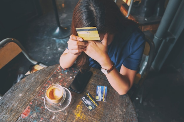 Closeup image of an asian woman get stressed and broke while holding credit card