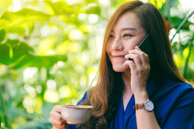 Closeup image of an asian woman holding and talking on mobile phone while drinking coffee in the garden