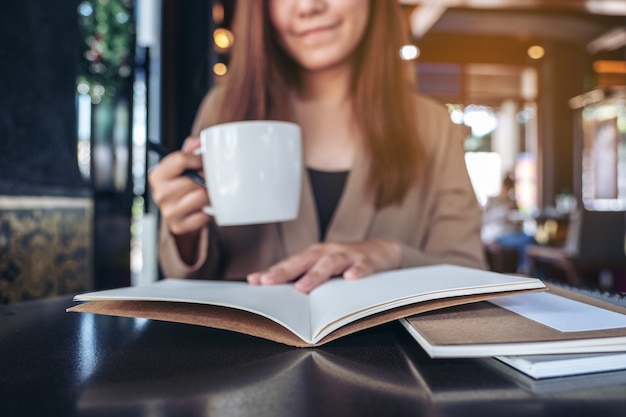 Closeup image of an asian woman reading and opening a book while drinking coffee in cafe