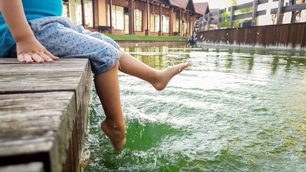 Closeup image of barefoot little toddler boy sitting on the wooden bridge at lake and splashing water with his feet