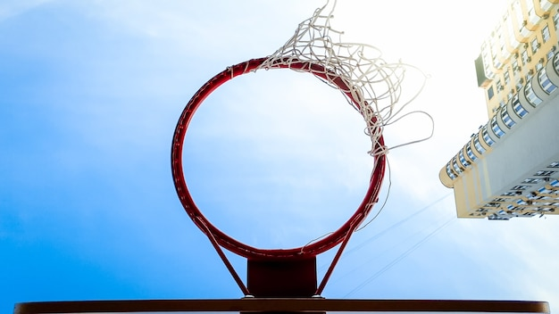 Closeup image of basketball ring with net against blue sky and high building in city living district