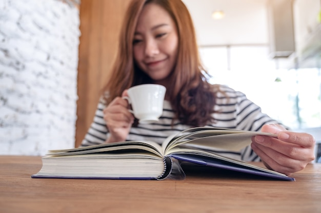 Closeup image of a beautiful asian woman holding and reading a book while drinking coffee