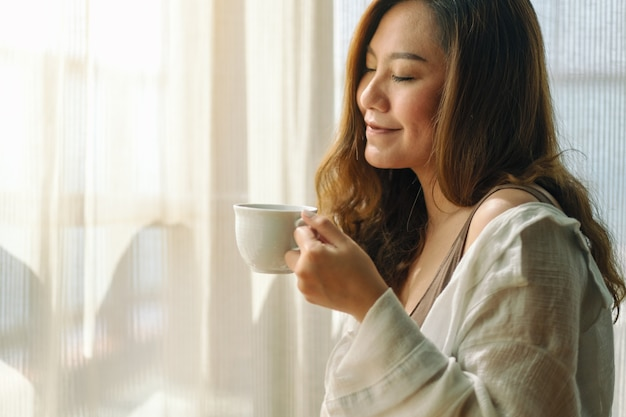 Closeup image of a beautiful asian woman holding and smelling a cup of hot coffee with feeling relaxed in the morning Premium Photo