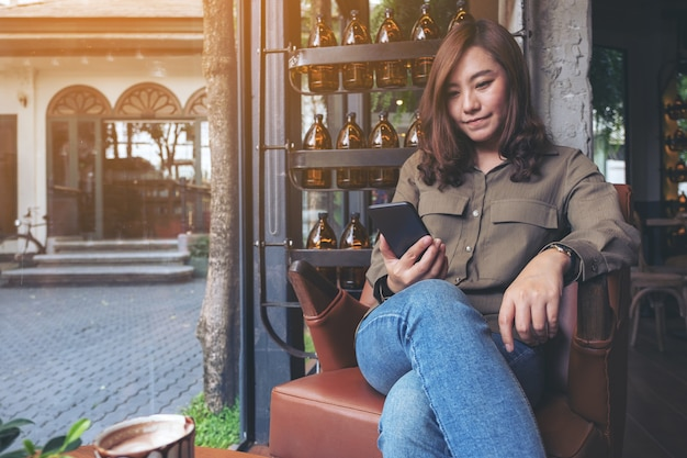 Closeup image of a beautiful asian woman holding , using and looking at smart phone in cafe
