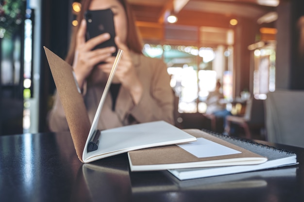 Closeup image of a beautiful asian woman holding , using and looking at smart phone while working in office
