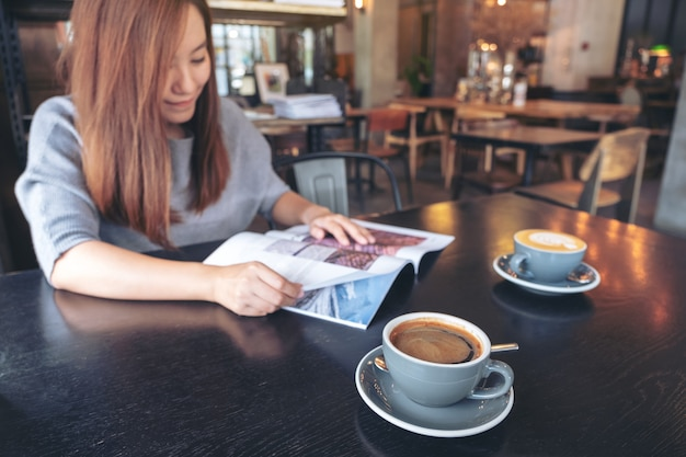 Closeup image of a beautiful asian woman reading magazine with coffee cup on table in modern cafe