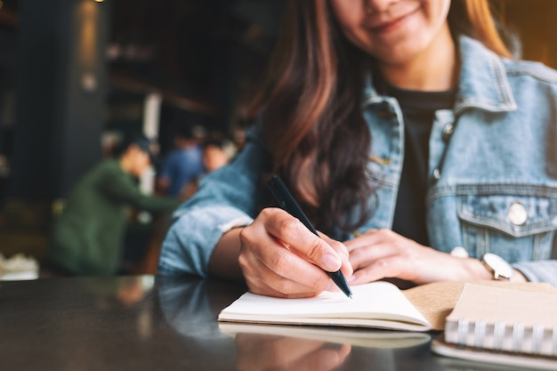 Closeup image of a beautiful asian woman writing on a blank notebook on the table