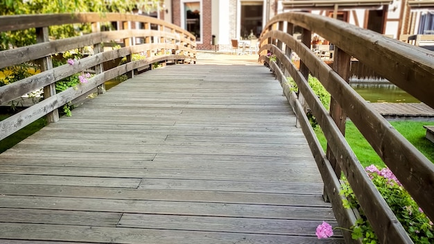 Closeup image of beautiful old wooden bridge across small calm river in old european town