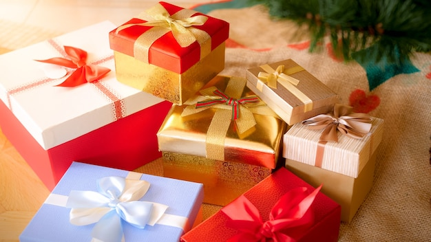 Closeup image of big pile of colorful christmas gift boxes tied with ribbons lying on floor at living room