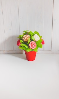 Closeup image of bouquet in red pot made from cupcakes against white wooden background. beautiful shot of sweets and pastry over white background