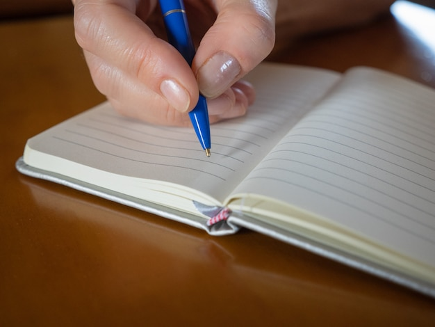 Closeup image of business woman writing on blank notebook on wooden table background.