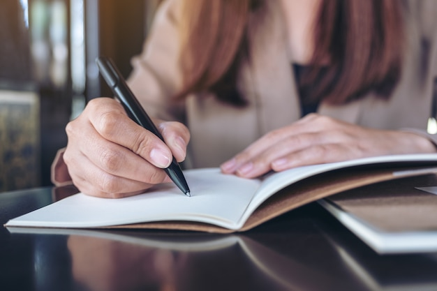 Closeup image of a business woman writing on blank notebook on wooden table