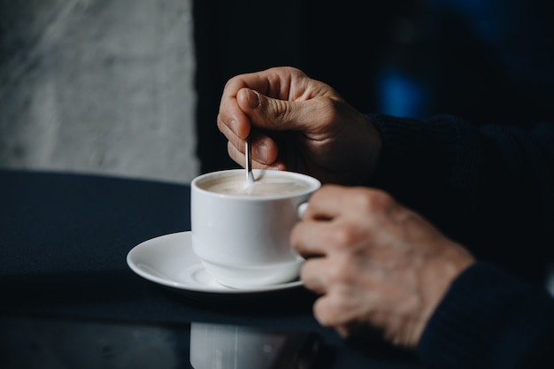 Closeup image of a businessman`s hands with coffee. closeup ,selected focus of man hand holding and stirs sugar in a white cup of coffee ,relaxtion tine concept.