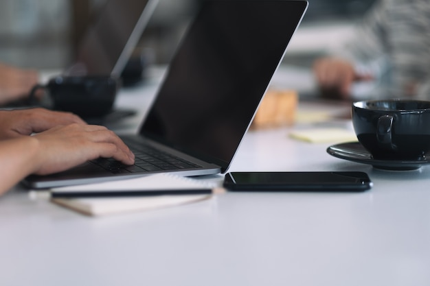 Closeup image of businessman using and working on laptop computer together in office