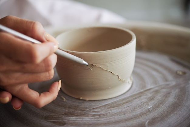 Closeup image of ceramist removing controlled amounts of clay from wheelthrown clay pot with ribbon ...