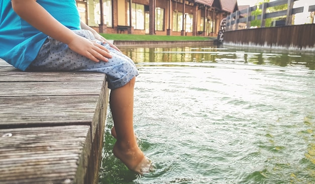 Closeup image of child sitting on the wooden pier at tiver and holding feet in water. kids playing and splashing water with legs