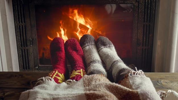 Closeup image of couple in knitted socks warming by the fireplace at house