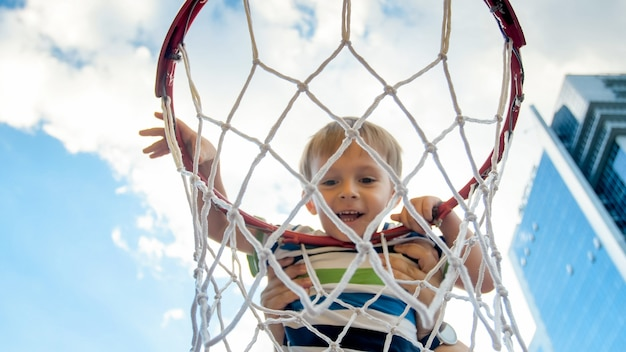 Closeup image of cute smiling toddler boy holding and hanging on basketball ring on sportrs playground at city