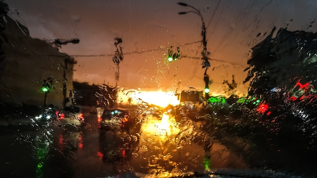 Closeup image of droplets on wet car windshield in rain at sunset light. abstract shot of wet windscreen an sun rays