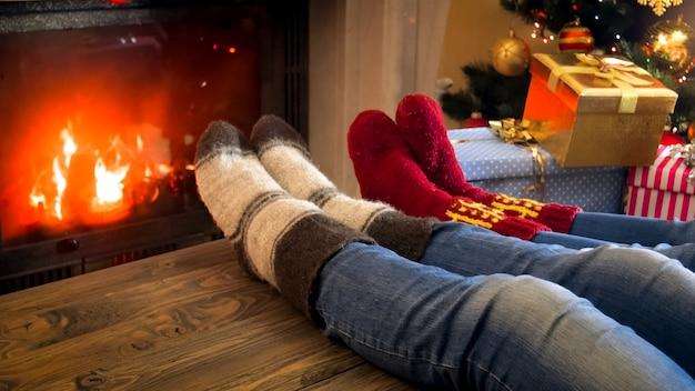 Closeup image of family feet in woolen socks lying on wooden table next to burning fireplace