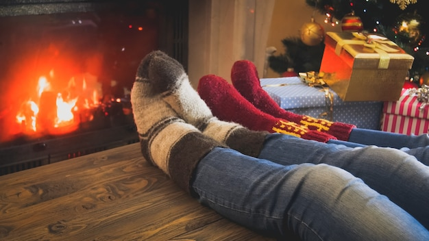 Closeup image of family in knitted woolen socks holding feet on wooden table next burning fireplace at room decorated for christmas