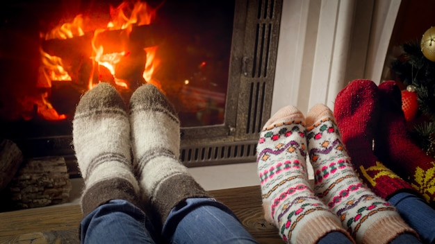 Closeup image family wearing knitted wool socks warming feet at fireplace next to decorated christmas tree