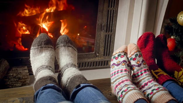 Closeup image of family with child in woolen socks warming by the burning fire