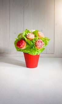 Closeup image of flowers in bouquet made of cupcakes and cakes on table at cafe or bakery. beautiful shot of sweets and pastry over white background