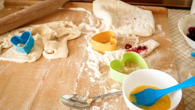 小麦粉、生地、調理器具、キッチンで調理やベーキングのための材料で覆われた木製の机の上の高角度からのクローズアップ画像