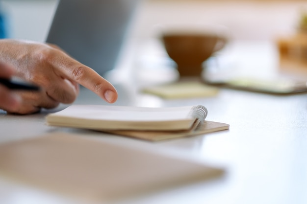 Closeup image of a hand pointing finger at notebook on the table