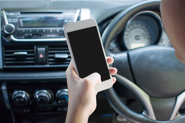 Closeup image of a hand using a smartphone on a car while driving