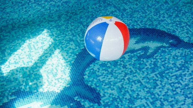Closeup image of inflatable beach ball in swimming pool. perfect image to illustrate summer beach vacation on holidays