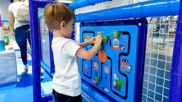 Closeup image of little toddler boy solving puzzle on the children palyground at amusement park. concept of smart kids and clever new generation