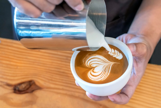 Closeup image of male hands barista pouring milk make coffee latte art in coffee shop