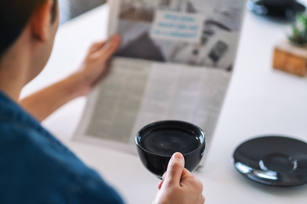 Closeup image of a man reading newspaper and drinking coffee in the morning
