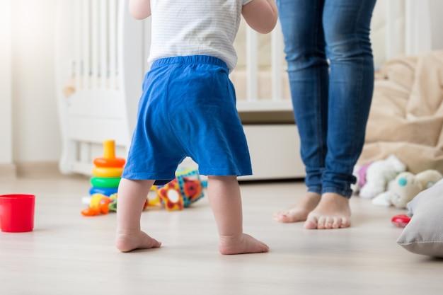 Крупным планом изображение 10-месячного мальчика, делающего первые шаги дома
