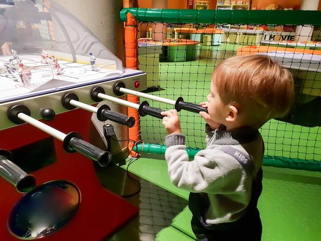 Крупным планом изображение 3-летнего маленького мальчика, играющего в настольный хоккей в парке развлечений