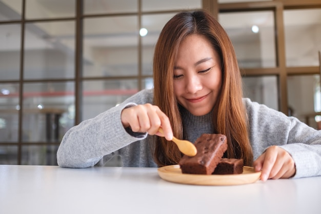 スプーンでおいしいブラウニーケーキを食べる美しいアジアの女性のクローズアップ画像