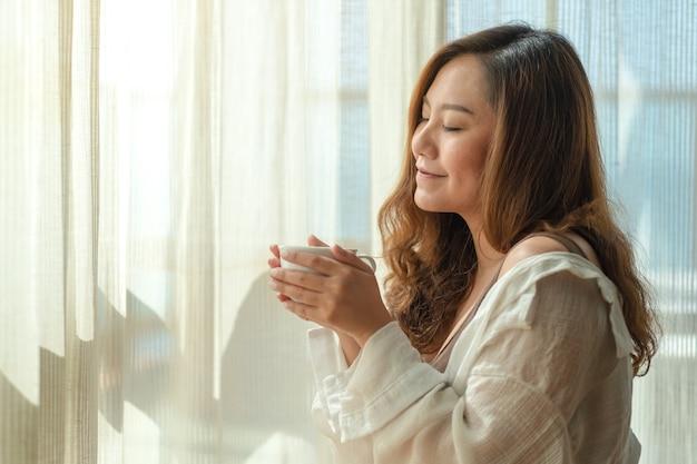 아침에 편안한 느낌으로 뜨거운 커피 한 잔을 들고 냄새 맡는 아름다운 아시아 여자의 근접 촬영 이미지