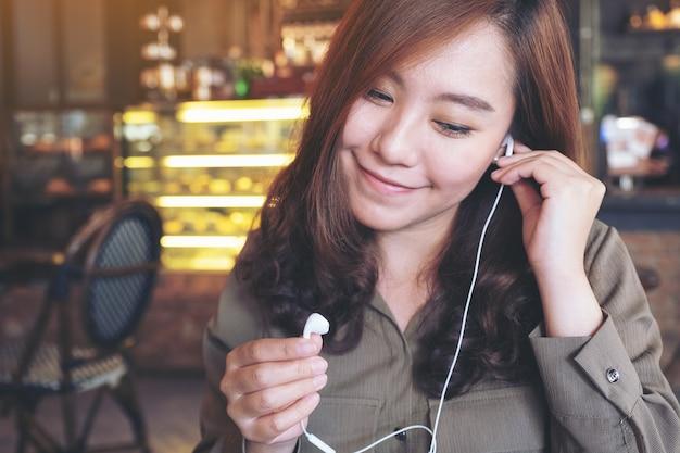 カフェで音楽を聴きながらイヤホンを保持している美しいアジアの女性のクローズアップ画像
