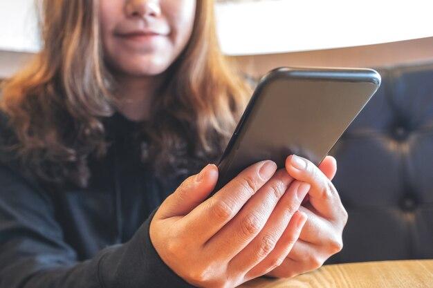 幸せな気分でスマートフォンを持って、使用して、見て美しいアジアの女性のクローズアップ画像