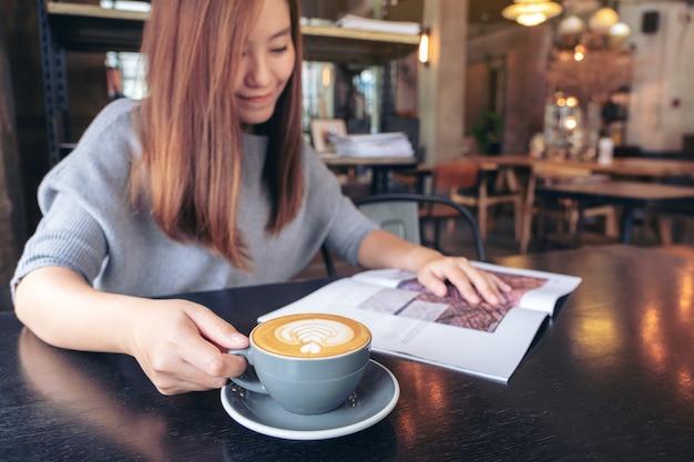 Крупным планом изображение красивой азиатской женщины, читающей журнал, попивая кофе в современном кафе